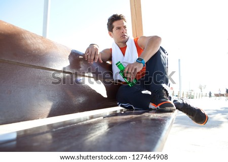 Portrait of a sports man relaxing sitting down on a wooden bench and holding a bottle of water, against a sunny sky. - stock photo