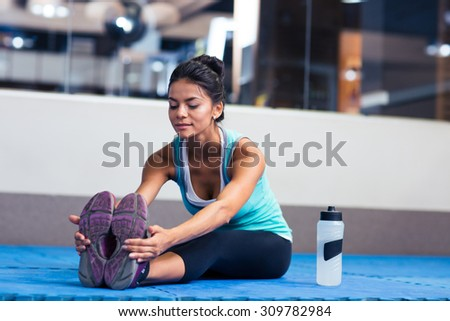 Portrait of a sports woman stretching in gym - stock photo