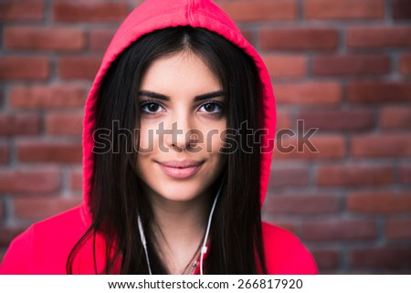 Portrait of a sporty cute woman in headphones over brick wall. Looking at camera - stock photo