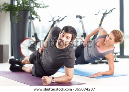 Portrait of a sporty man and woman training together at the gym.