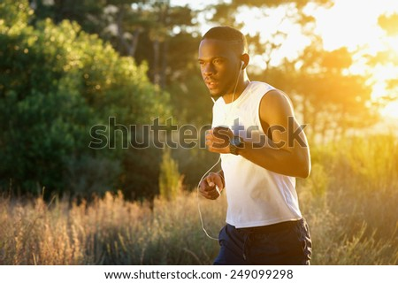Portrait of a sporty young man running outdoors in nature - stock photo