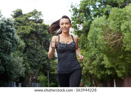 Portrait of a sporty young woman running outdoors - stock photo
