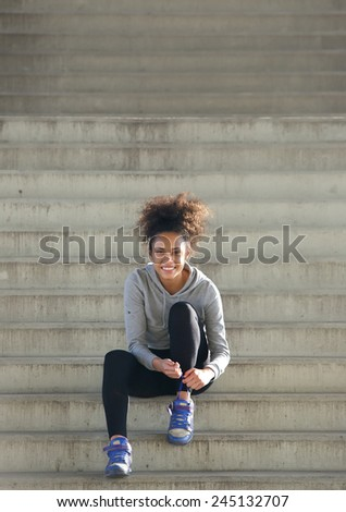 Portrait of a sporty young woman sitting on steps tying shoe lace