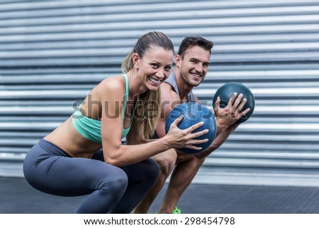 Portrait of a squatting muscular couple doing ball exercise - stock photo