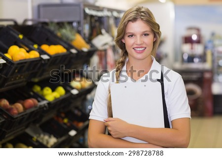 Portrait of a staff woman having a clipboard on her hands at supermarket