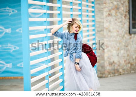 Portrait of a standing smiling girl with blond hair, bright pink lips and nude make up leaning on blue and white stripes fence on the background looking down wearing blue denim shirt, grey tulle skirt - stock photo