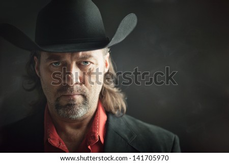 Portrait of a stern looking cowboy. - stock photo