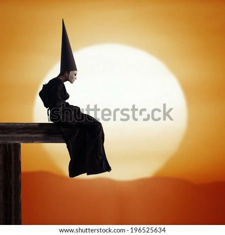 Portrait of a strange person in black cloak and dunce hat at sunset - stock photo