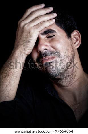 Portrait  of a stressed and desperate young man suffering a strong headache on a black background - stock photo
