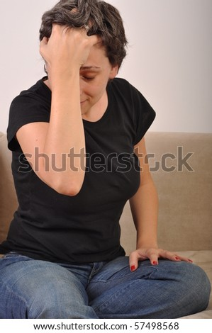 portrait of a stressed woman holding head on the couch