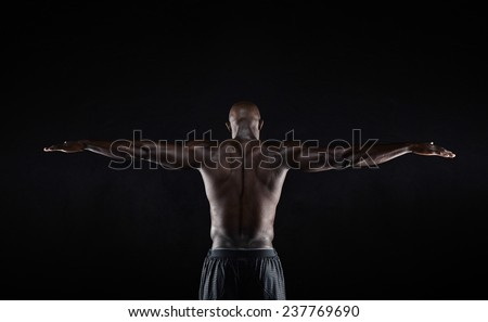 Portrait of a strong back of a black muscular man stretching his arms against black background. Rear view of african fitness model with masculine physique - stock photo