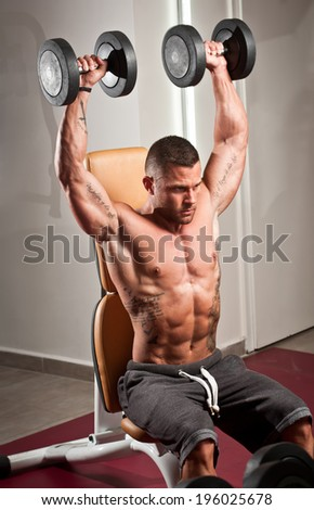 Portrait of a strong fit young man exercising in a gym. - stock photo