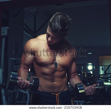 Portrait of a strong guy doing exercises with dumbbells - stock photo