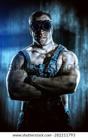 Portrait of a strong muscular man coal miner standing over dark grunge background. Mining industry. Art concept.