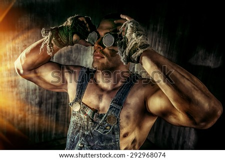 Portrait of a strong muscular man coal miner standing over dark grunge background. Mining industry. Art concept. - stock photo