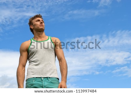 Portrait of a strong young man on blue sky background.