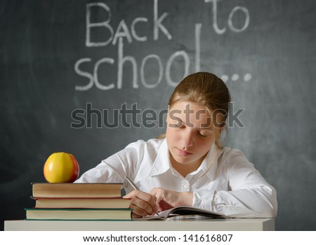 Portrait of a student or schoolgirl siting at desk against blackboard