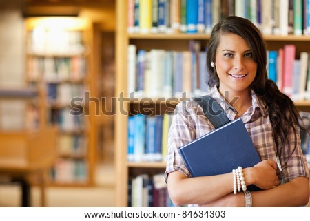 Portrait of a student posing with a book in the library - stock photo