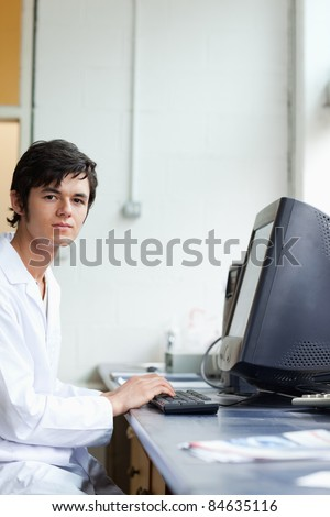 Portrait of a student posing with a monitor in a laboratory