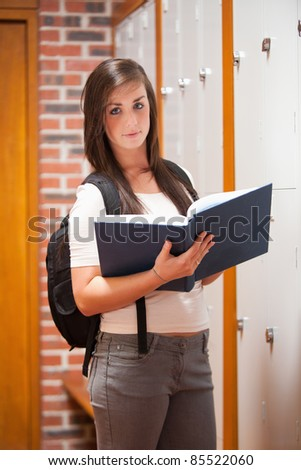 Portrait of a student reading a book in a corridor