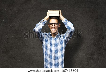 portrait of a student with books on his head against a grunge background - stock photo