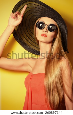 Portrait of a stunning fashionable lady over bright yellow background. Beauty, fashion concept. Optics. - stock photo
