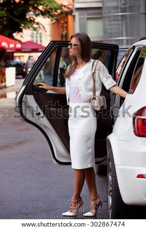 Portrait of a stunning fashionable model near the white car. Luxury life. Business, elegant businesswoman.
