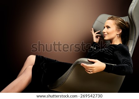 Portrait of a stunning fashionable model sitting in a chair in Art Nouveau style. Business, elegant businesswoman. Interior, furniture. - stock photo