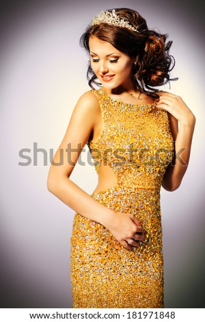 Portrait of a stunning woman in luxurious golden dress.  - stock photo