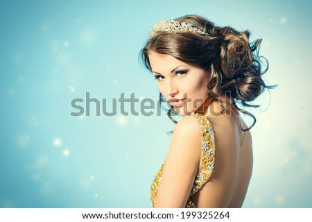Portrait of a stunning woman in luxurious golden dress.  - stock photo