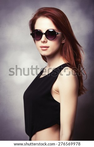 Portrait of a style redhead women in sunglasses and black dress on grey background.