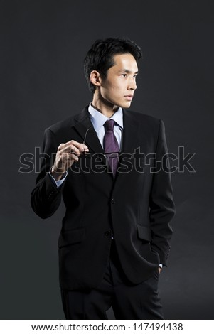 Portrait of a stylish Asian business man standing in front of a dark grey background - stock photo
