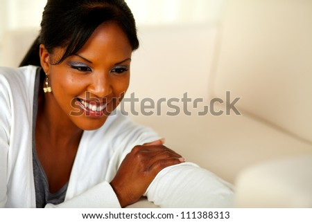 Portrait of a stylish black female looking down at home indoor. With copyspace