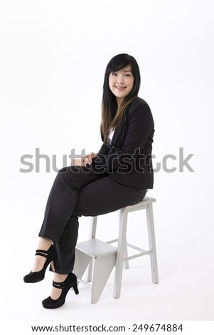 Portrait of a stylish Chinese Businesswoman sitting on a stool. Isolated on white background. Asian brunette female model. - stock photo