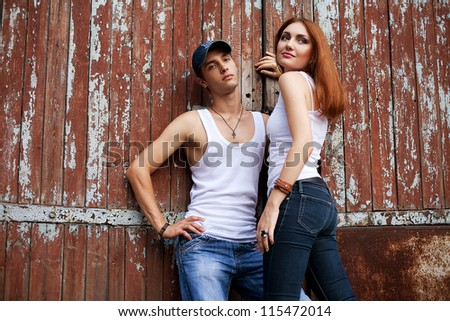 portrait of a stylish couple in jeans standing near wooden house. outdoor shot - stock photo