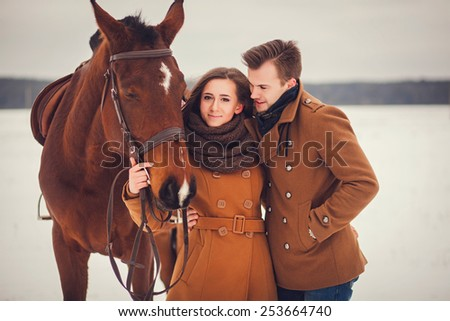 Portrait of a stylish couple with a horse in a field - stock photo