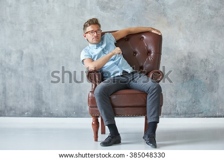 Portrait of a stylish intelligent man stares into the camera, small unshaven, charismatic, blue shirt, sitting on a brown leather chair, dialog, negotiation, short sleeve, brutal, hairstyle - stock photo