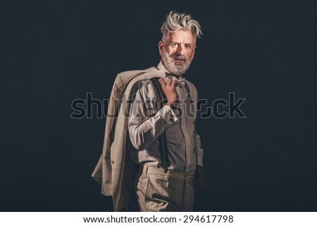 Portrait of a Stylish Matured Man Holding his Coat Over his Shoulder and Looking at the Camera Against Black Background. - stock photo