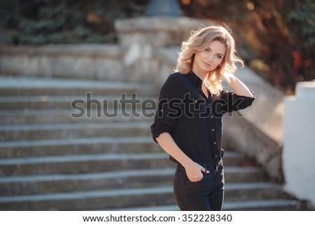 Portrait of a Stylish Pretty Young Woman in Autumn Fashion walking the city Looking at the Camera.Fashion woman. Beautiful fashionable woman standing on the city street. Fashion Look. autumn. warm. - stock photo