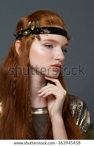 Portrait of a stylish redhead woman posing over gray background - stock photo