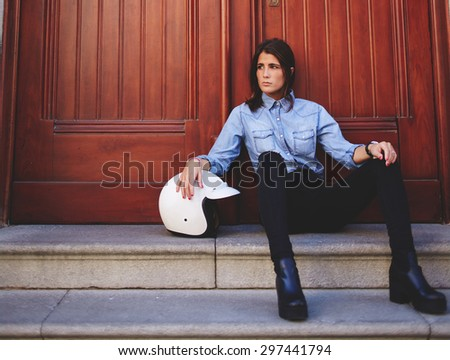 Portrait of a stylish young biker woman rests after racing in the city outdoors, attractive trendy model sitting on stairs against of brown wooden door with copy space for your text message or content - stock photo