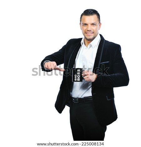 Portrait of a stylish young man pointing on cup over white background - stock photo