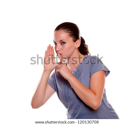 Portrait of a stylish young woman requesting silence looking at you on blue shirt on isolated background - stock photo