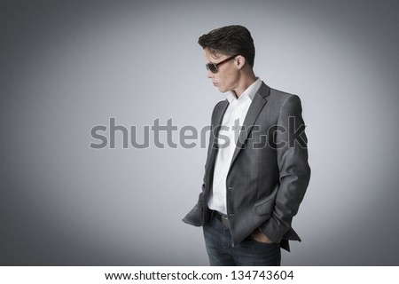 Portrait of a suave handsome man in a stylish suit and sunglasses standing sideways with his hands in his pockets lost in though on a grey background with corner vignetting and copy space - stock photo
