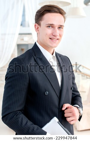 Portrait of a successful and confident businessman. Young man in formal wear holding a the tablet and smiling at the camera while his colleague talking on the background - stock photo