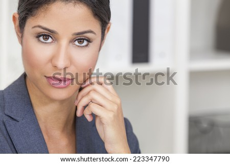 Portrait of a successful beautiful young Latina Hispanic woman or businesswoman in her office - stock photo
