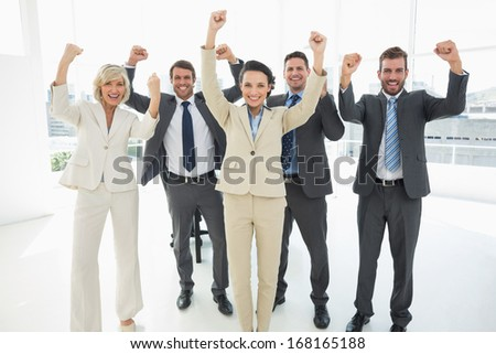 Portrait of a successful business team clenching fists in a bright office - stock photo