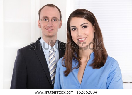Portrait of a successful business team - he in suit and tie and she smiling in a blue blouse - teamwork - stock photo