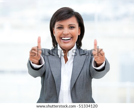 Portrait of a successful business woman with thumbs up in the office - stock photo