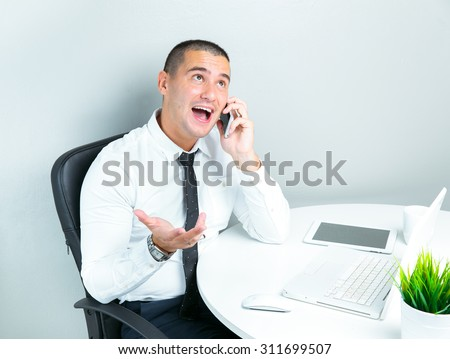 portrait of a successful businessman at office using mobile phone